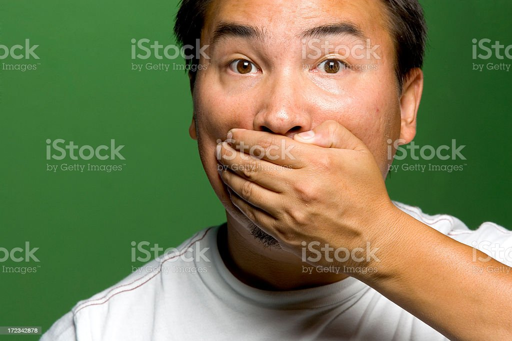Adult male putting his hand over his mouth not speaking stock photo