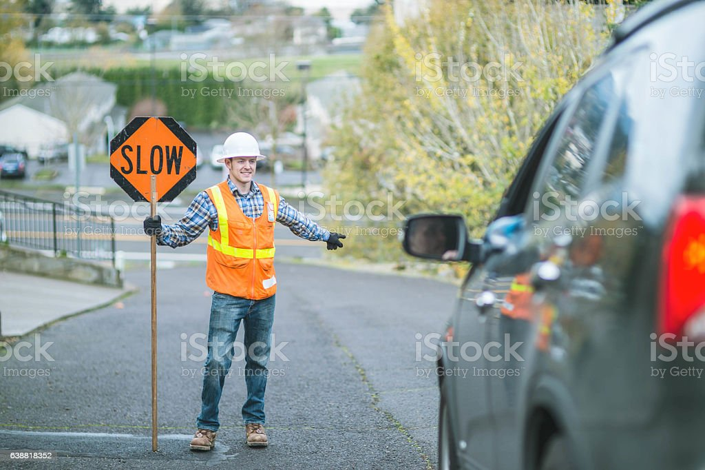 Adult male road flagger is cheerfully flagging a vehicle stock photo