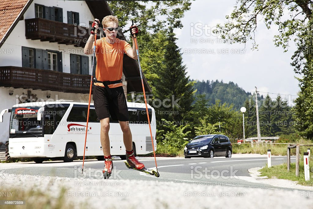 Adult male roller skiing on Slovenia main road royalty-free stock photo