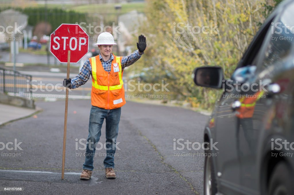Adult male street flagger directing traffic stock photo