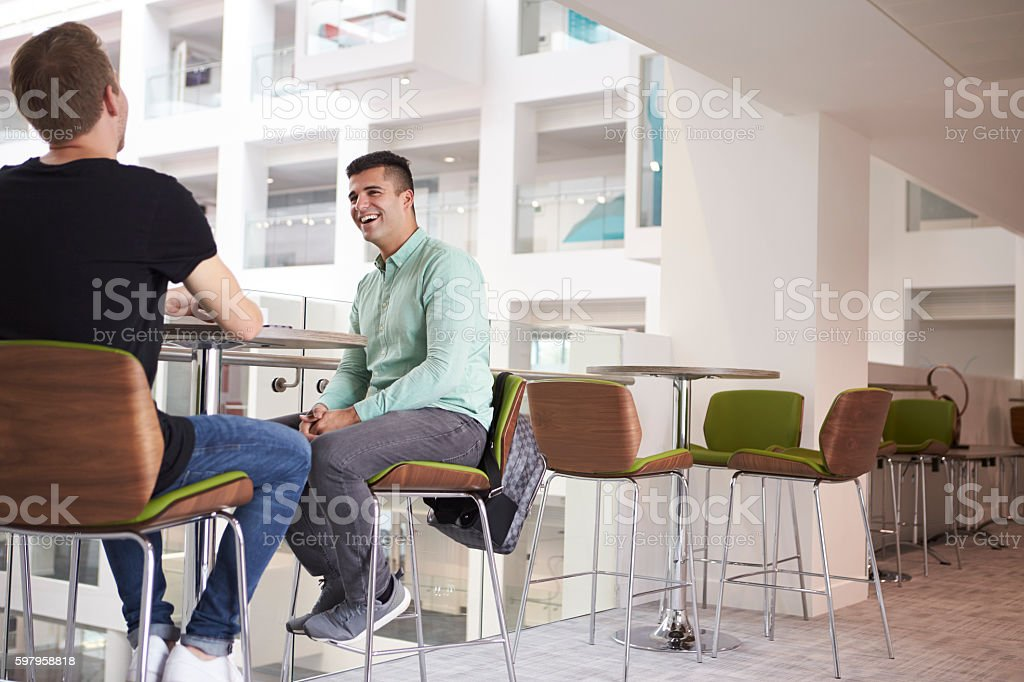 Adult male students talking at a university cafe, low angle stock photo
