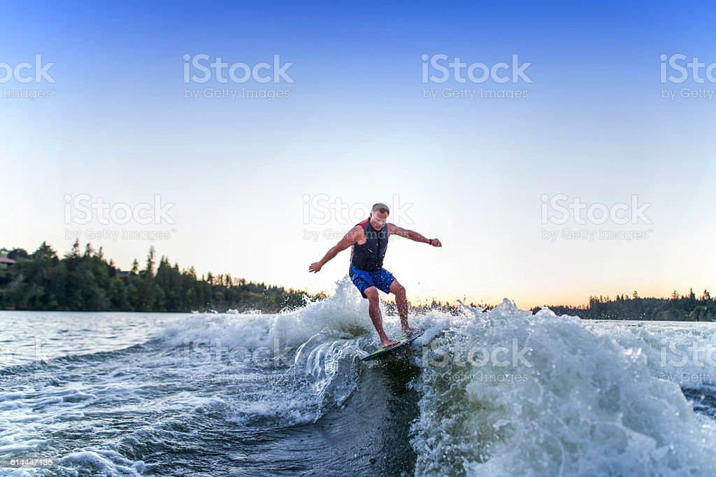 Adult male wake surfing behind a ski boat stock photo