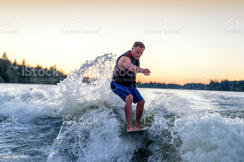 Adult male wake surfing stock photo
