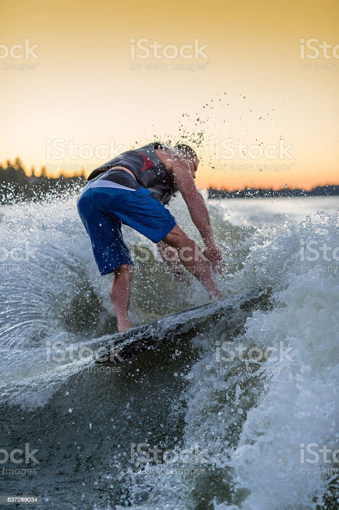Adult male wakesurfing at sunset on giant wake stock photo