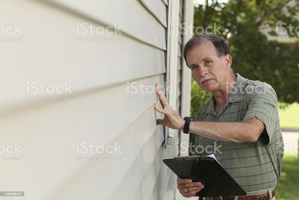 Adult male with clipboard inspects vinyl siding on residential home stock photo