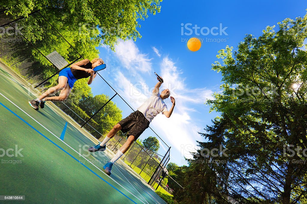 Adult Man and Woman Pickleball Player Playing Pickleball in Court stock photo