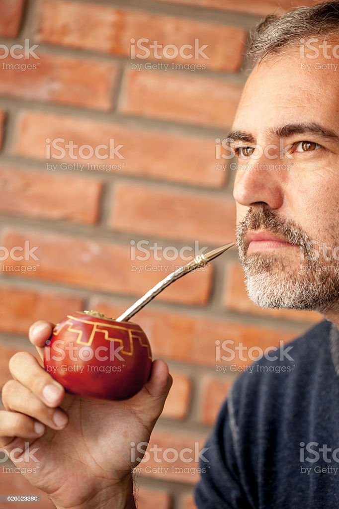 Adult Man Drinking Mate Tea from Traditional Mate Cup stock photo