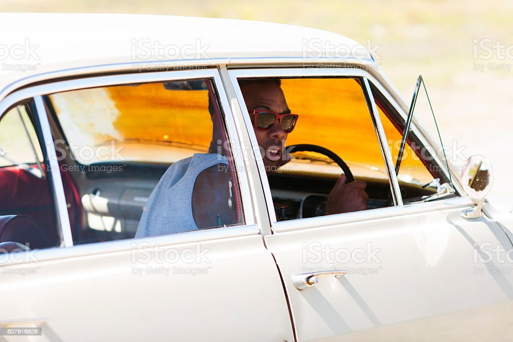 Adult Man Driving His Vintage Car At Daytime stock photo