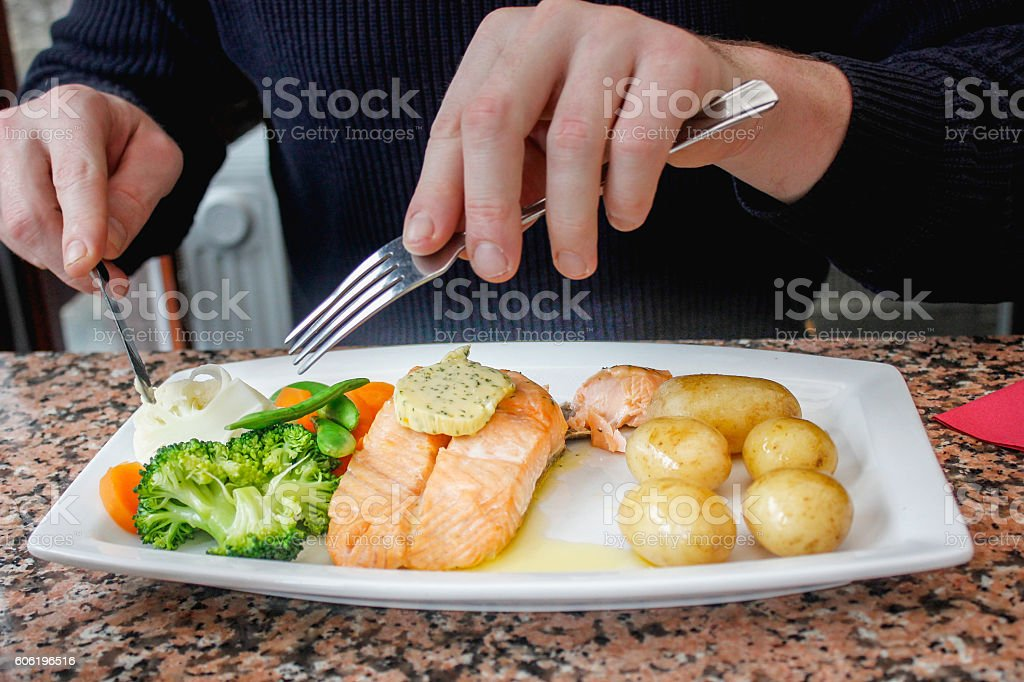 Adult man eating salmon steak and vegetables stock photo