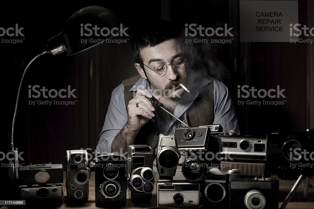 Adult man fixing at old Fashioned camera repair service stock photo
