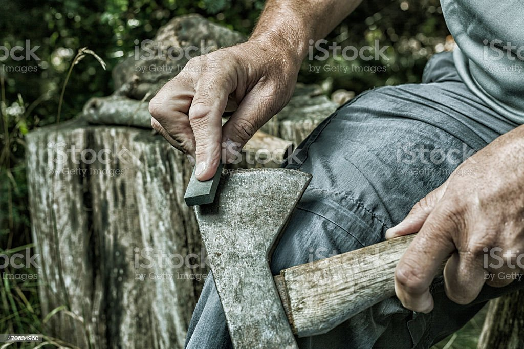 Adult Man Hands Sharpening Rusty Axe with Whetstone stock photo