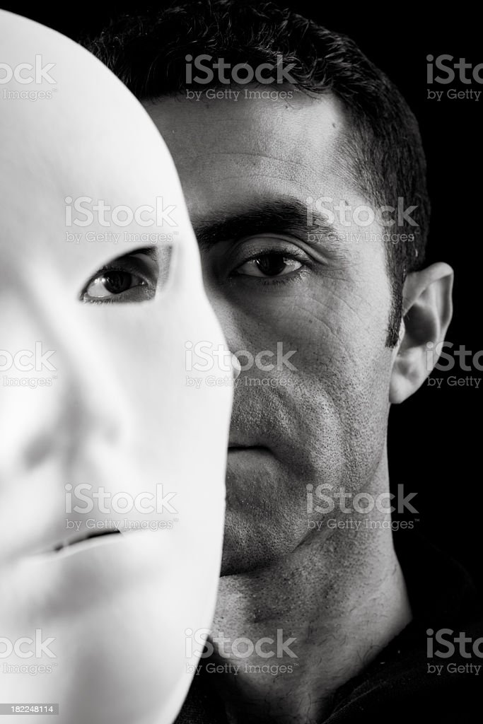 Adult Man Hiding Behind A White Mask In Dark royalty-free stock photo