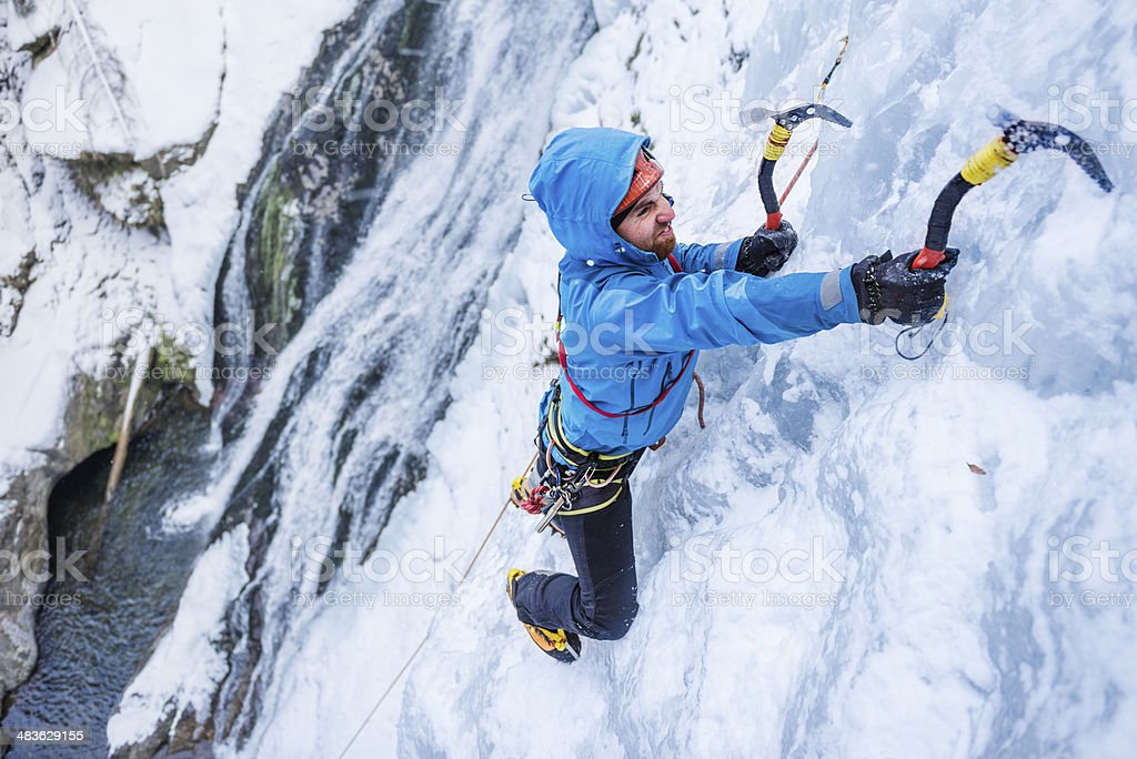 Adult man ice climbing a frozen cascade stock photo