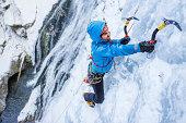 Adult man ice climbing a frozen cascade