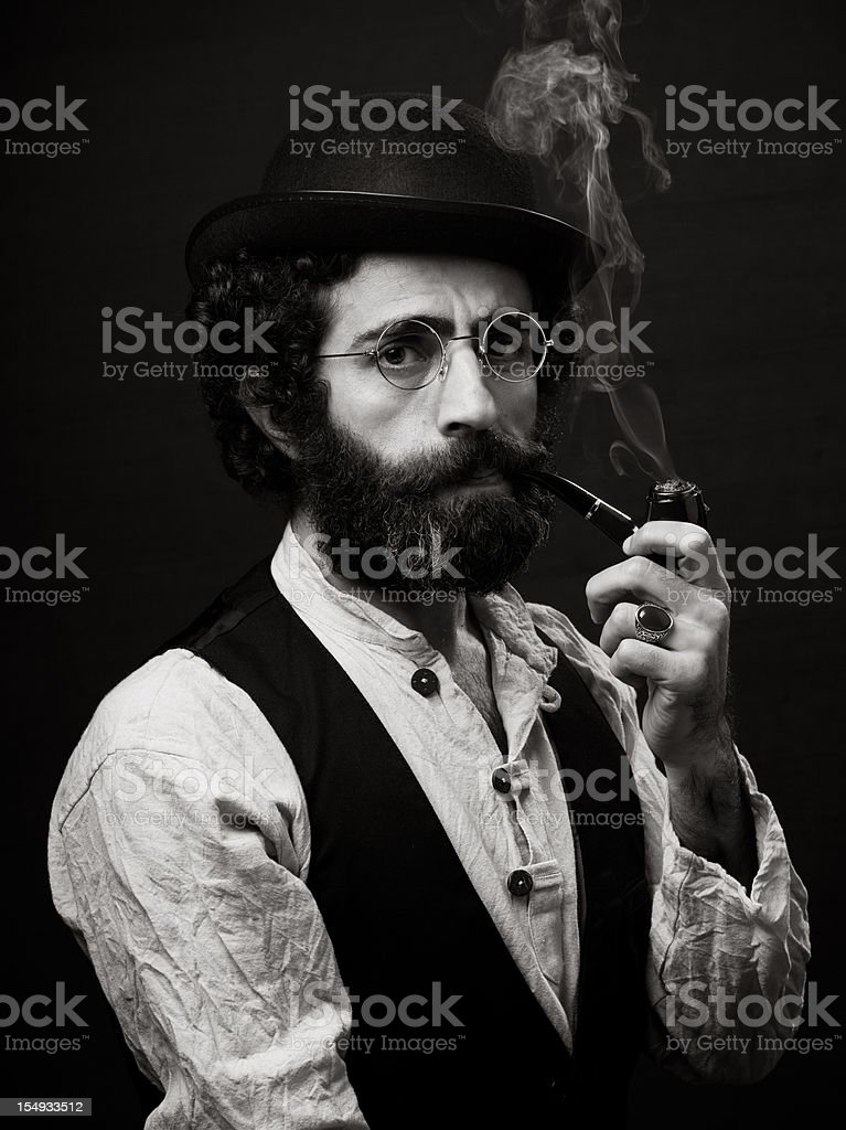 Adult man in 1800s style costume smoking pipe stock photo