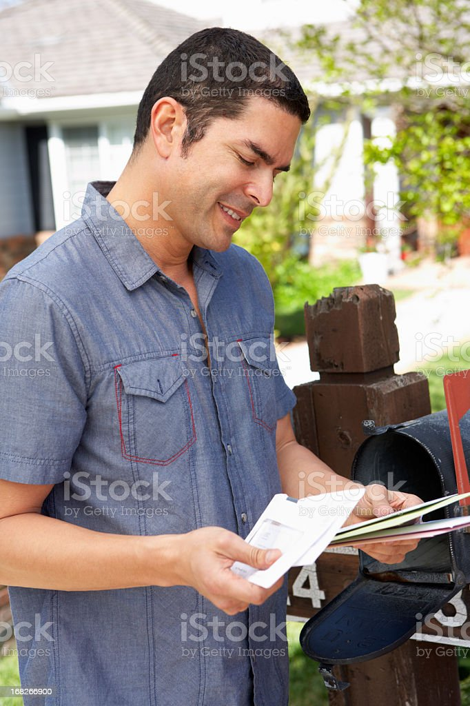 Adult man in denim shirt, outdoors, checking his mailbox stock photo