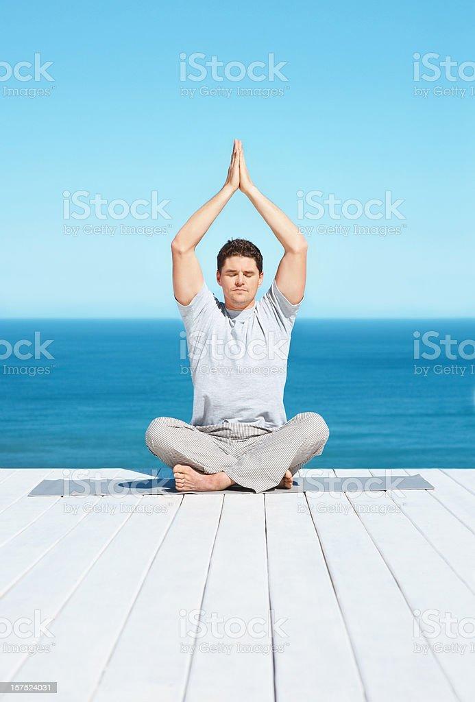 Adult man meditating on a dock royalty-free stock photo