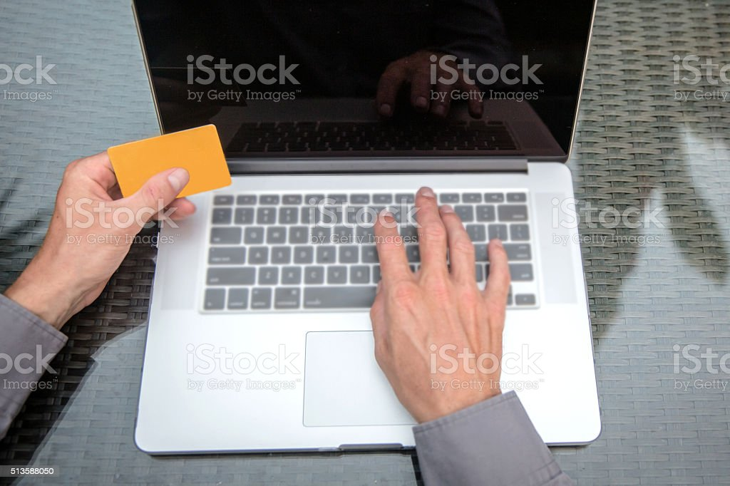 Adult man online shopping while typing stock photo