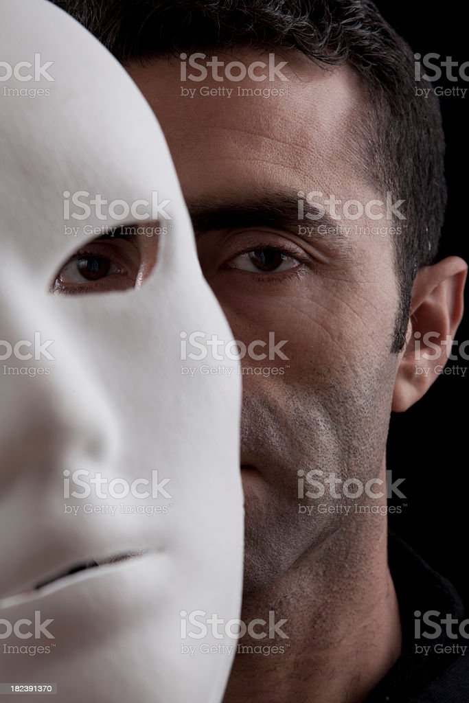 Adult Man Peeking Behind Mask In Vertical Composition royalty-free stock photo