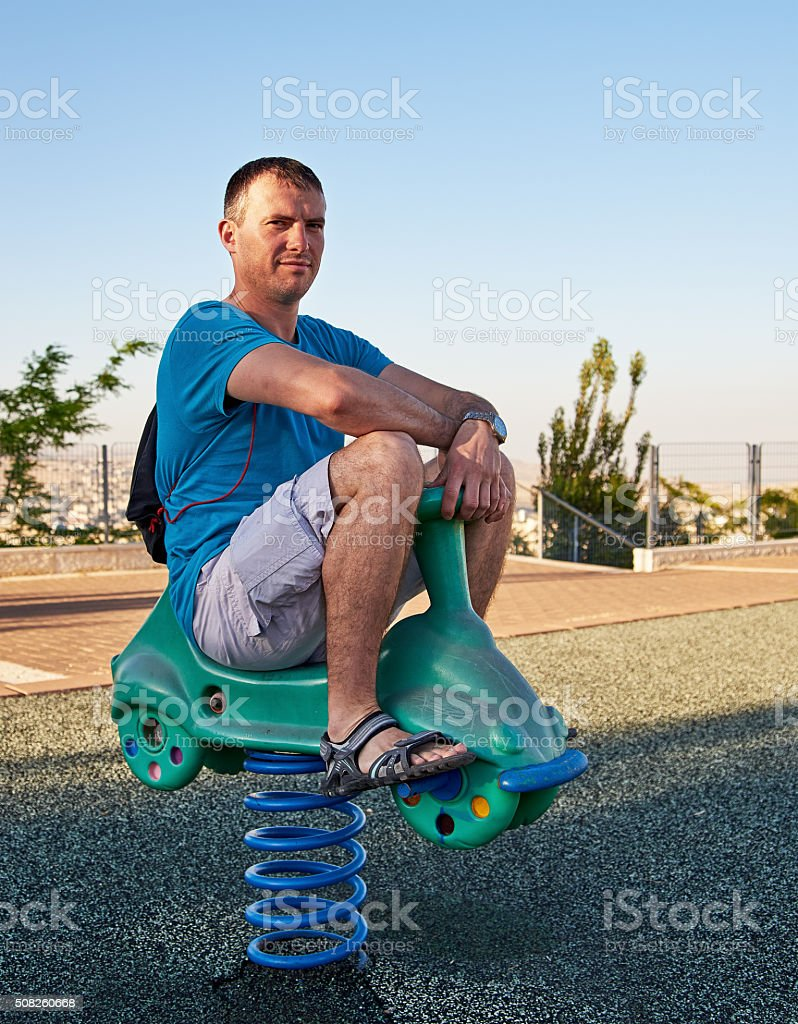 Adult man reliving childhood stock photo