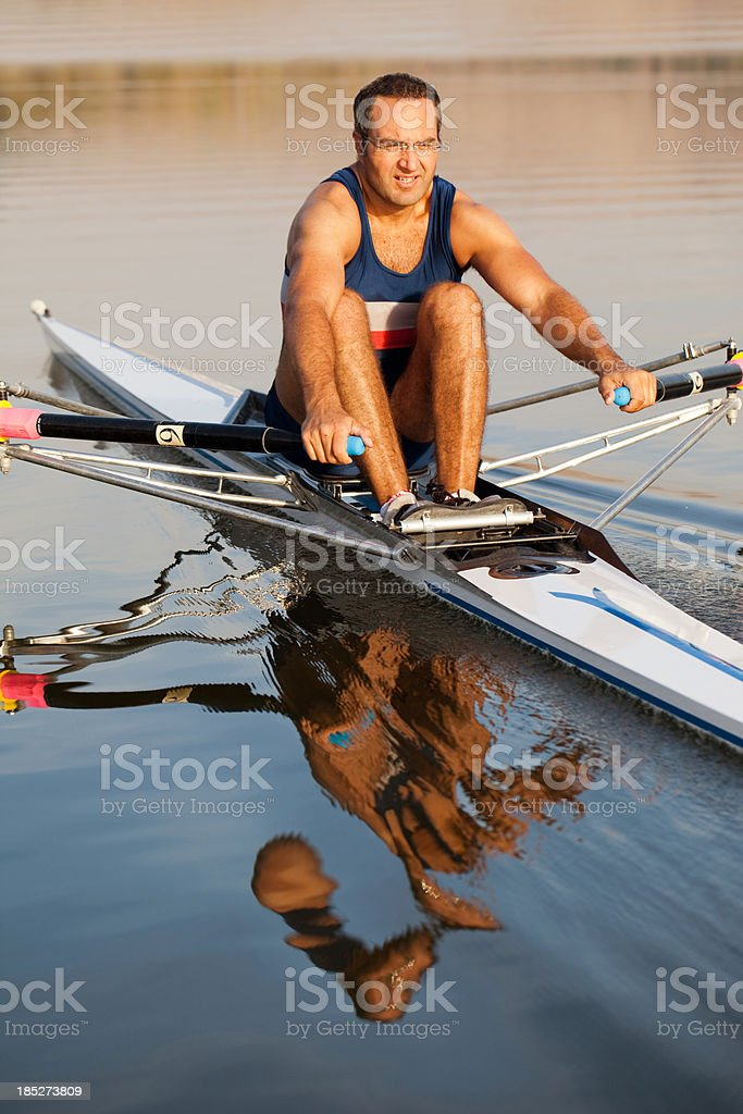 Adult man rowing sculling boat on lake stock photo