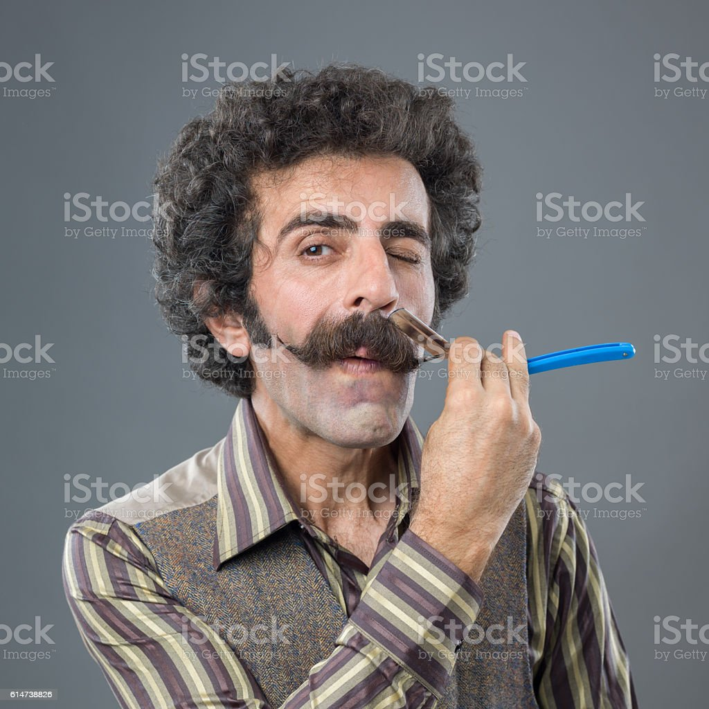 Adult man shaving his lovely mustaches with old fashioned razor stock photo