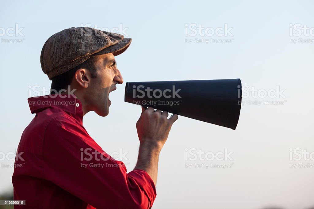 Adult Man Shourting Via Old Fashioned Megaphone stock photo
