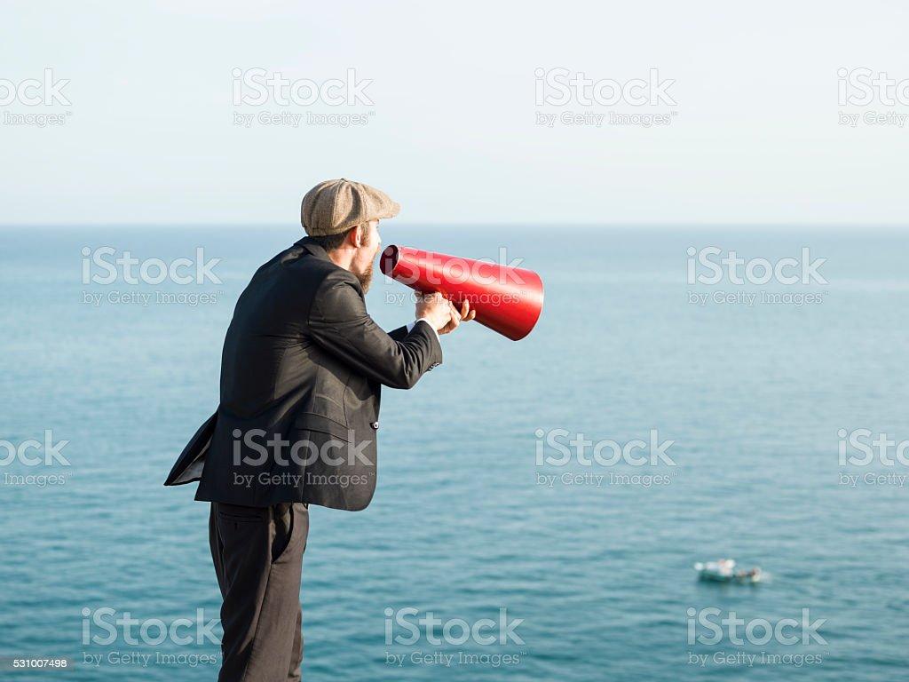 Adult Man Shouting Trough Megaphone Toward Sailing Boat stock photo