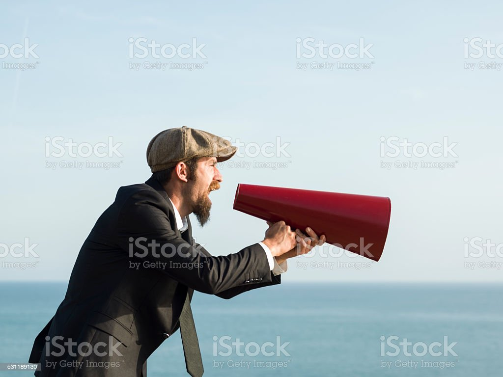 Adult Man Shouting Via Old Fashioned Megaphone In Outdoor stock photo