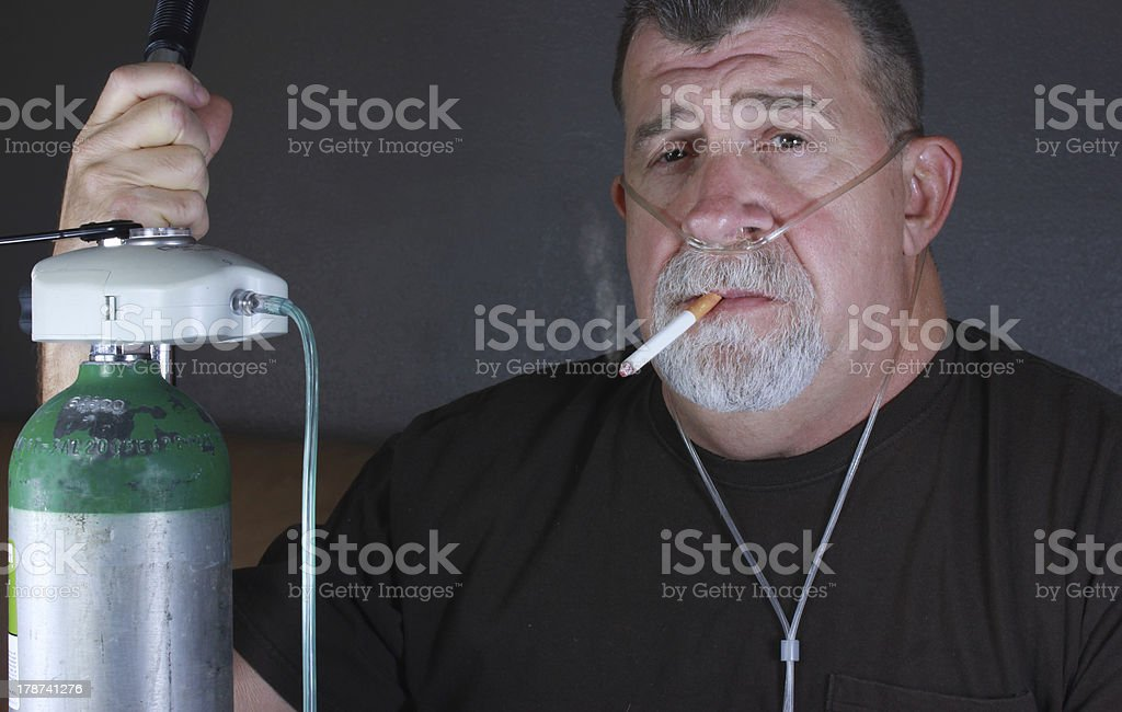 Adult Man Smoking with Cannula and Oxygen Tank stock photo