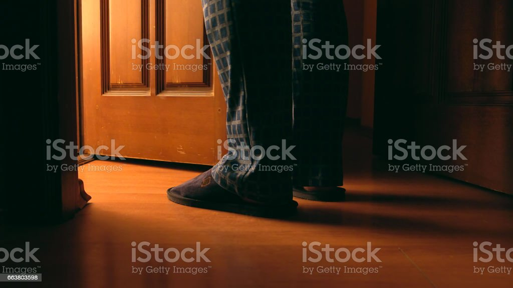 Adult man stands near door to a bathroom at the night stock photo