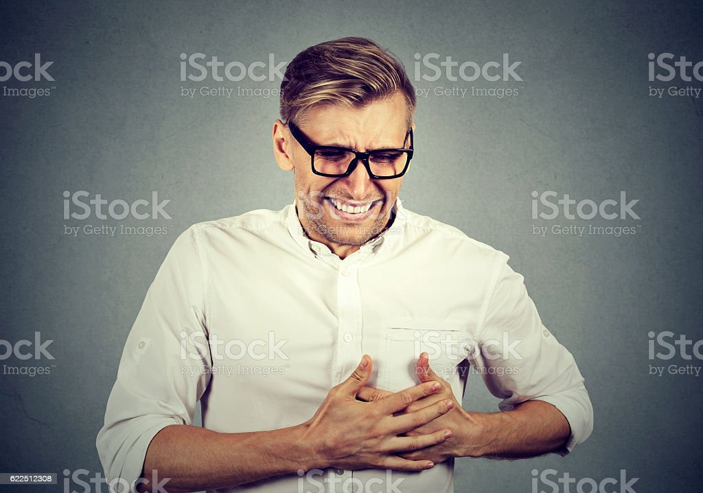 Adult man suffering from sharp heartache, chest pain stock photo
