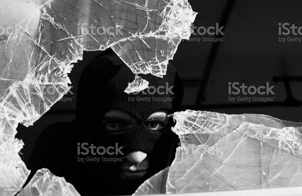Adult man wearing a snow mask peeking behind  broken glass stock photo