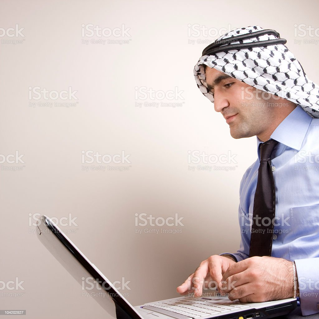 Adult Man Wearing Arabic Headscarf Using Computer royalty-free stock photo