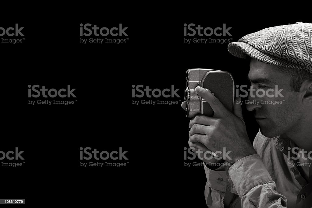 Adult Man Wearing Flat Cap Filming Via Old Fashioned Camera royalty-free stock photo