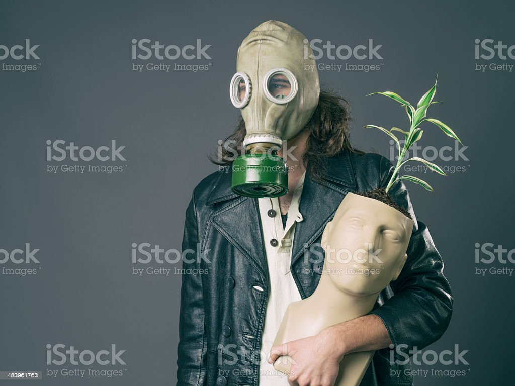 Adult man wearing gas mask holding mannequin pot with plant stock photo