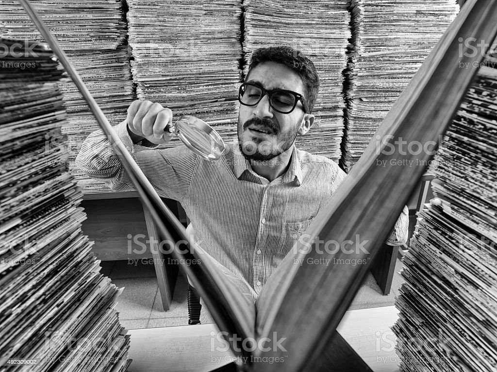 Adult man with dark hair reading large book in archive stock photo