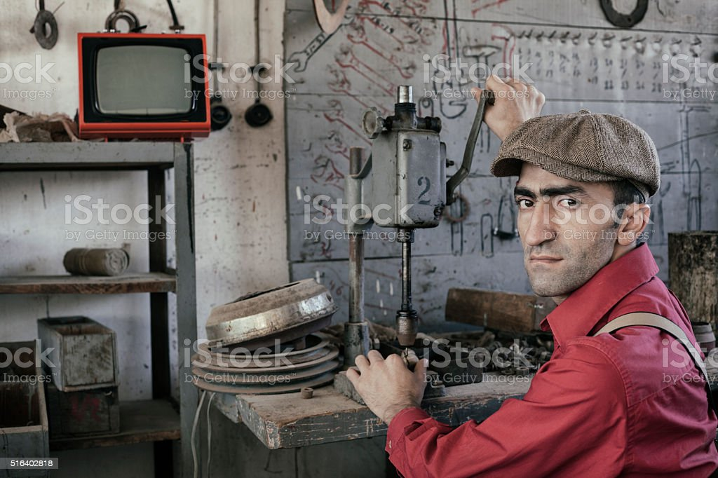 Adult man working in old fashioned garage stock photo