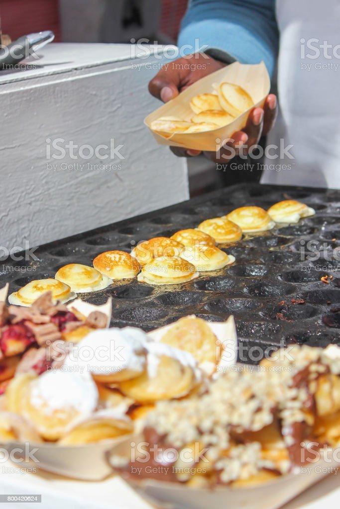 Adult men baking Sweet Dutch pancakes (poffertjes) stock photo