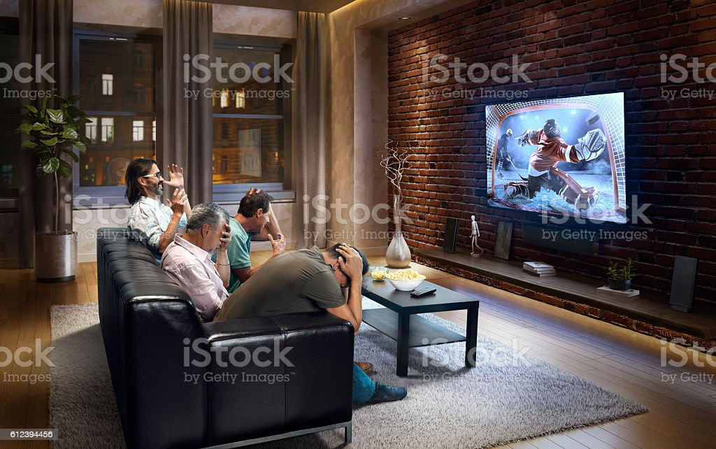 Four adult men upset while watching Ice hockey game on TV. They are...