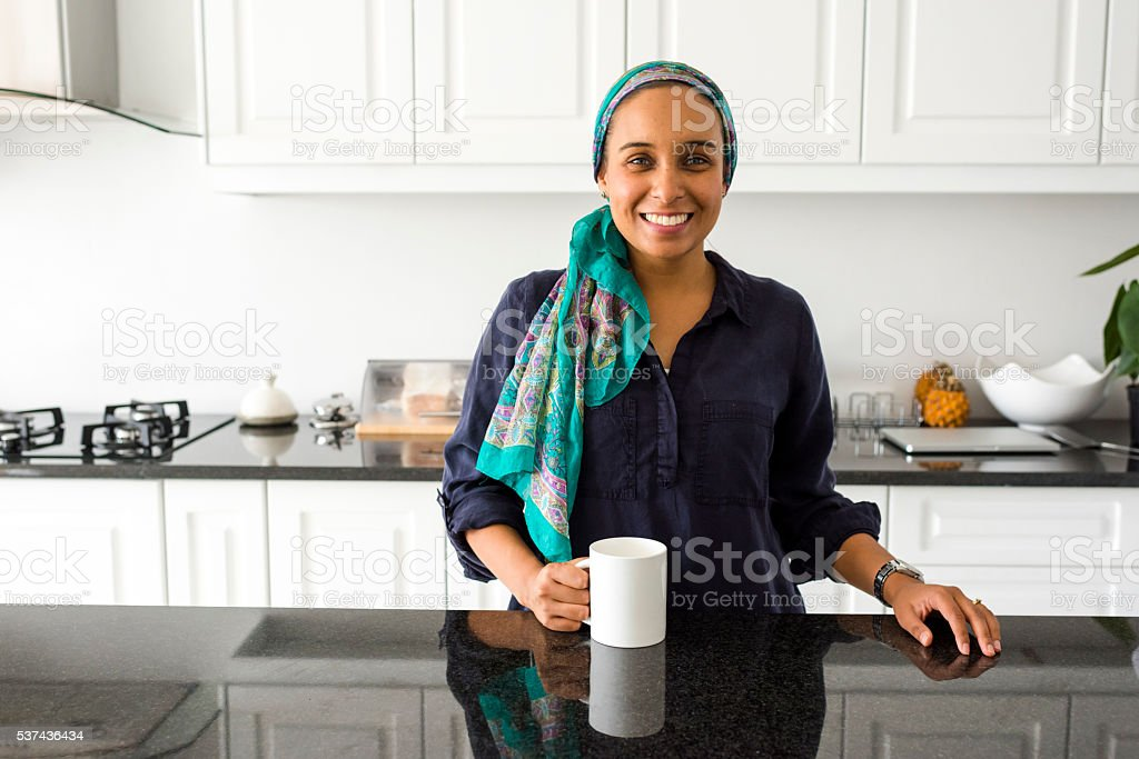 Adult Muslim Woman Drinking Coffee In Her Kitchen stock photo
