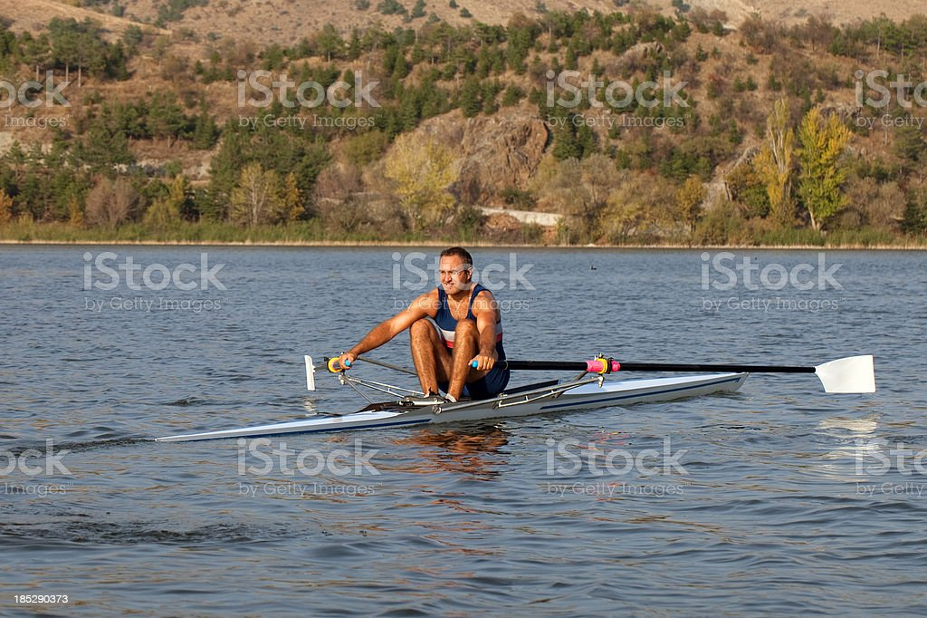 Adult Rower man rowing sculling boat on lake stock photo