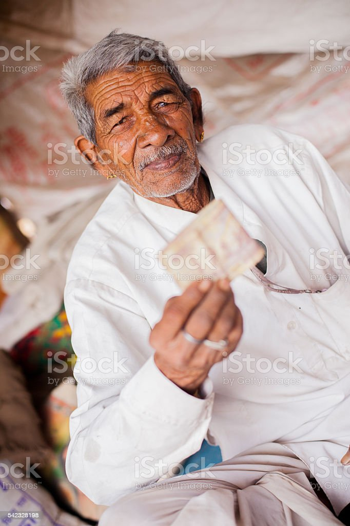 Adult Senior Indian Vendor Holding Rupees stock photo