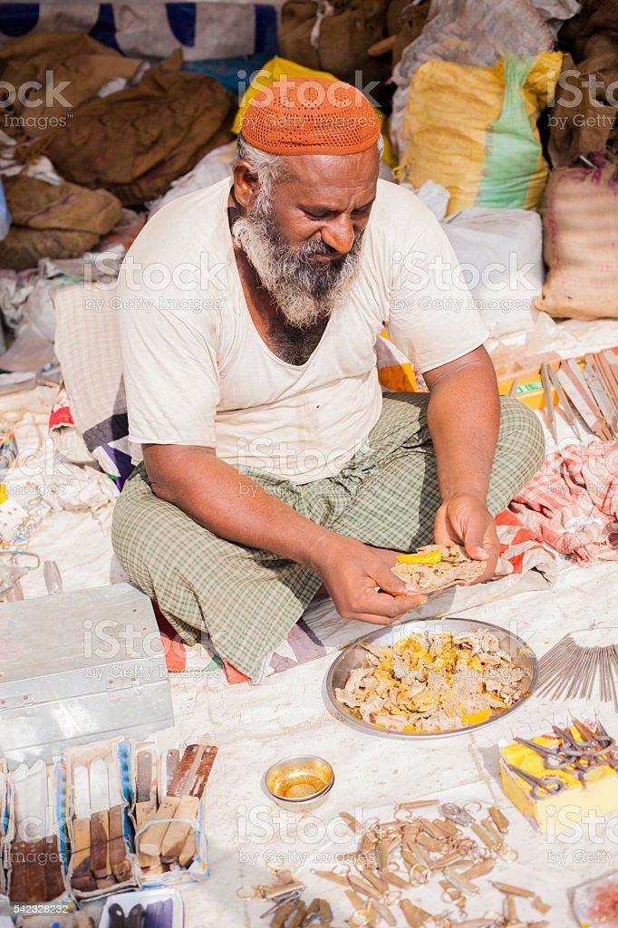 Adult Senior Indian Vendor On Lunch Break stock photo