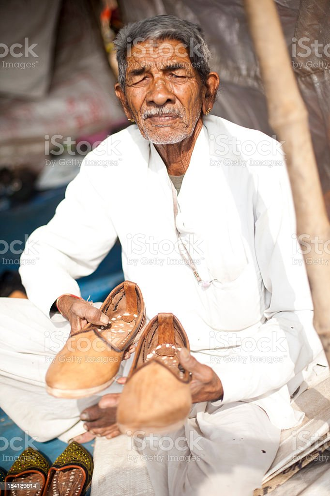 Adult Senior Indian Vendor Selling Shoes royalty-free stock photo