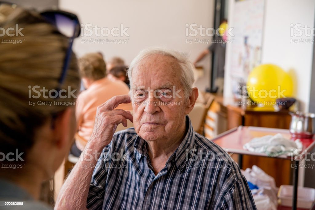 Adult Senior Talking With Young Lady At The Elderly Day Care Center stock photo