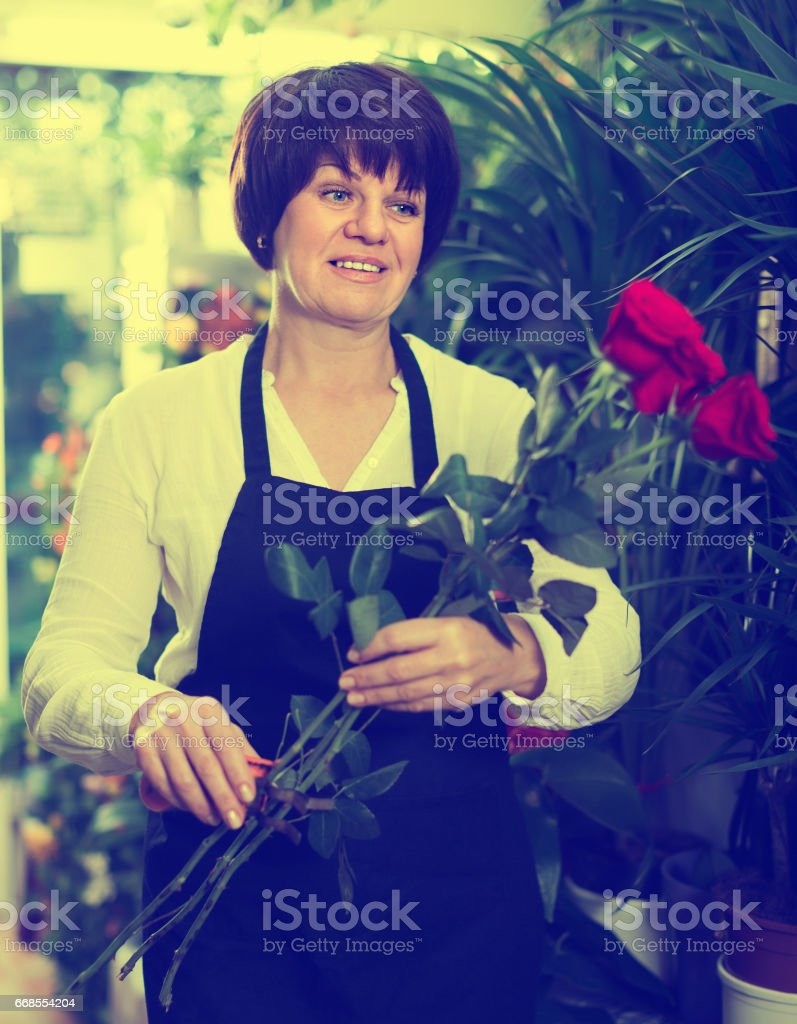 Adult shop assistant displaying bright red roses stock photo