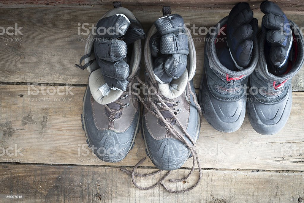 Adult snow boots alongside those of a child stock photo