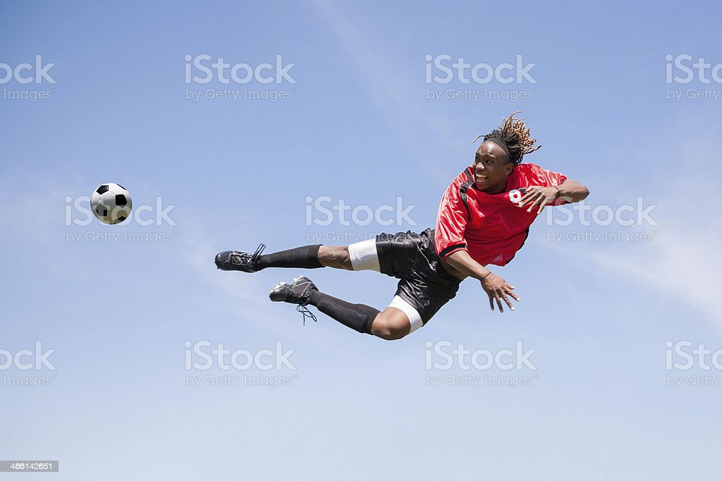 Adult soccer player kicking ball in mid-air during game royalty-free stock photo