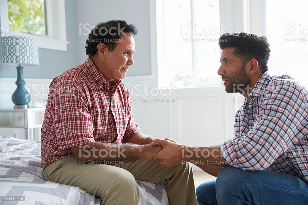 Adult Son Comforting Father Suffering With Dementia stock photo